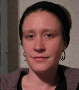Laurel, wearing black headband and hoop earrings