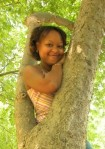 Photo of Patrice, smiling in a tree