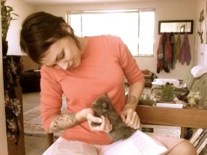 Jasmine in pink shirt holding small kitten