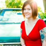 Kaity wearing red shirt sitting in front of car
