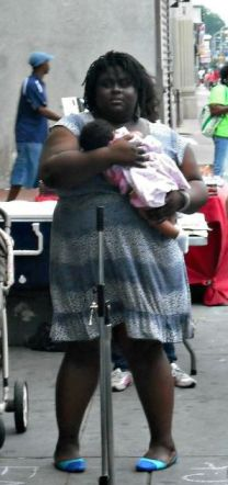 Iresha wearing a dress, holding a baby